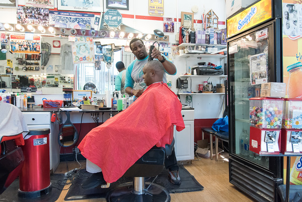05/24/18 Wesley Bunnell | Staff Johnny Turner works on cutting a clients hair at Blaze Barber Shop on Thursday afternoon. The barbershop is a place of discussion everyday including topics as the NFL's recent decision to require on field personnel to stand for the National Anthem.