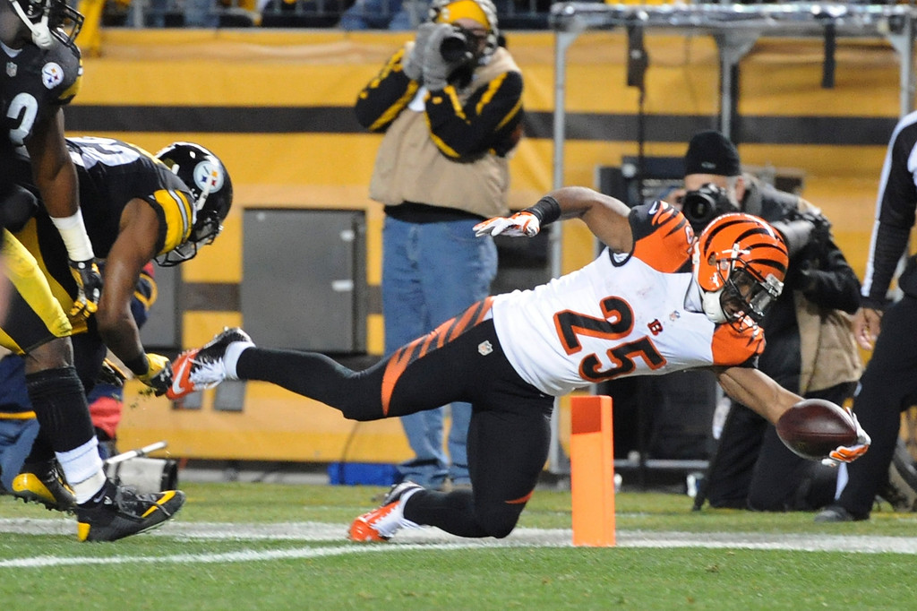 . Cincinnati Bengals running back Giovani Bernard (25) leaps for the end zone past Pittsburgh Steelers free safety Mike Mitchell (23) and scores a touchdown during the first quarter an NFL football game, Sunday, Dec. 28, 2014 in Pittsburgh. (AP Photo/Don Wright)