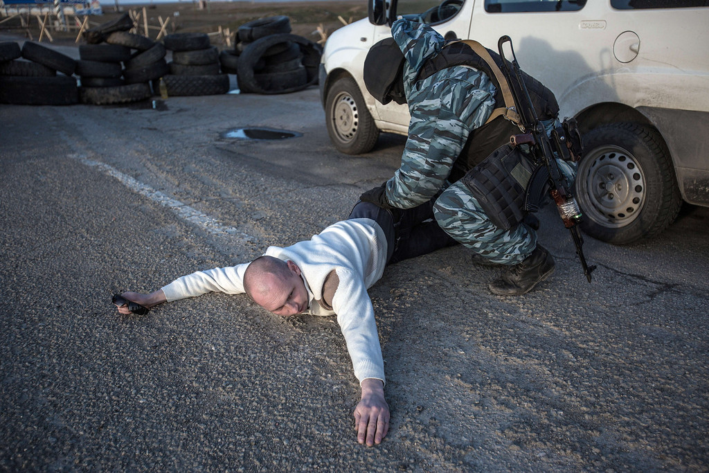 . A Pro-Russian serviceman searches a man at Chongar checkpoint blocking the entrance to Crimea on March 10, 2014. Russia vowed on March 10 to unveil its own solution to the Ukrainian crisis that would run counter to US efforts and would appear to leave room for Crimea to switch over to Kremlin rule. The unexpected announcement came as Ukraine\'s new pro-European leaders raced to rally Western support in the face of the seizure by Kremlin-backed forces of the strategic Black Sea peninsula and plans to hold a Sunday referendum on switching Crimea\'s allegiance from Kiev to Moscow. ALISA BOROVIKOVA/AFP/Getty Images