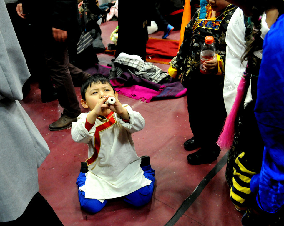 . Tenzin Woeser, 4, of Edina, plays his flute in front of friends during  Losar, celebration of the Tibetan New Year  at Augsburg College.  (Pioneer Press: Sherri LaRose-Chiglo)