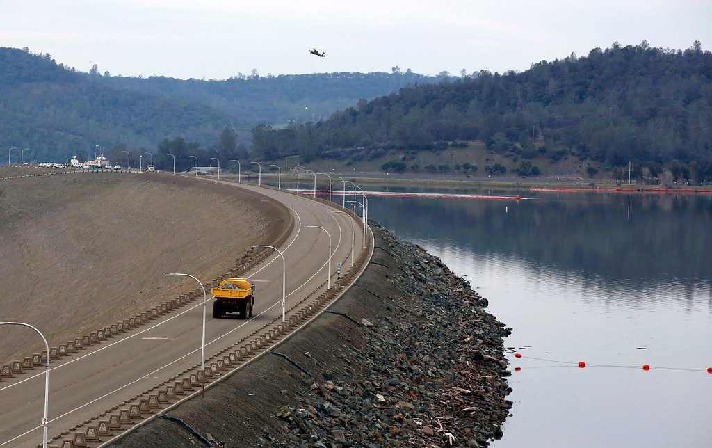 . A dump truck carrying a load of rocks crosses the Oroville Dam to be dropped in a hole on the lip of the dam\'s emergency spillway Monday Feb.13, 2017, in Oroville, Calif. The barrier, at the nation\'s tallest dam, is being repaired a day after authorities ordered mass evacuations for everyone living below the lake out of concerns the spillway could fail and send a 30-foot wall of water roaring downstream. (AP Photo/Rich Pedroncelli)