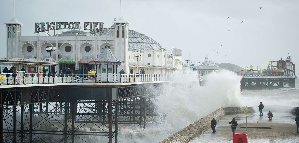 . People look on as large waves crash against the walls of Brighton seafront, in southern England on October 27, 2013 as a predicted storm starts to build. Britain was braced on October 27 for its worst storm in a decade, with heavy rain and winds of more than 80 miles (130 kilometres) an hour set to batter the south of the country.  EON NEAL/AFP/Getty Images