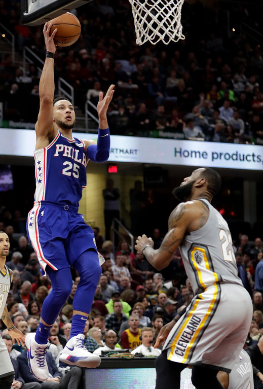 . Philadelphia 76ers\' Ben Simmons (25), from Australia, shoots over Cleveland Cavaliers\' LeBron James (23) in the second half of an NBA basketball game, Thursday, March 1, 2018, in Cleveland. (AP Photo/Tony Dejak)