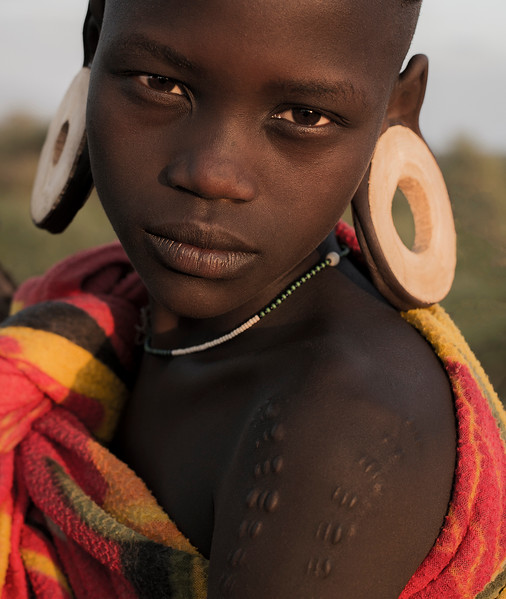 A young Murci girl wearing the traditional earnings made of clay.  Omo Valley, Ethiopia, 2017.