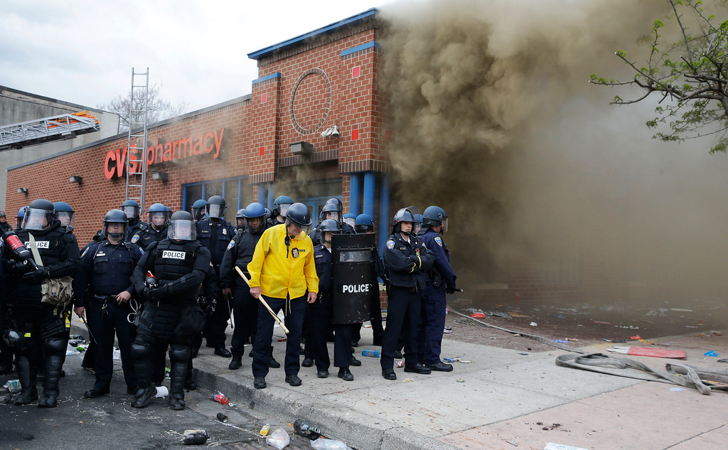 . Police stand in front of a burning store, Monday, April 27, 2015, during unrest following the funeral of Freddie Gray in Baltimore. Gray died from spinal injuries about a week after he was arrested and transported in a Baltimore Police Department van. (AP Photo/Patrick Semansky)