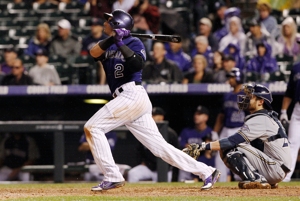 . Colorado Rockies\' Troy Tulowitzki, left, follows the flight of his solo home run with Milwaukee Brewers catcher Jonathan Lucroy in the eighth inning of a baseball game in Denver on Saturday, July 27, 2013. (AP Photo/David Zalubowski)