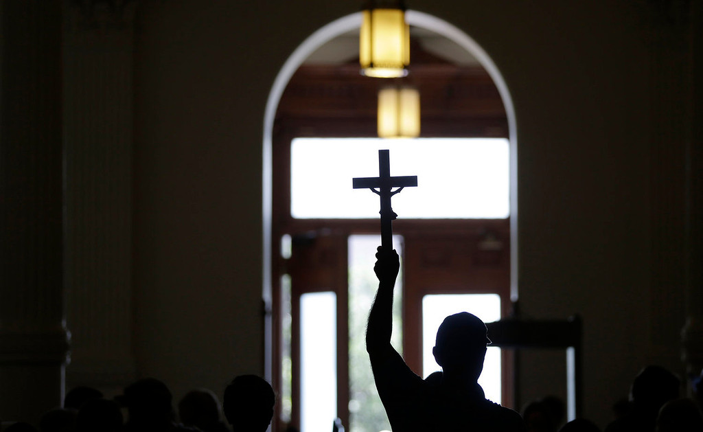 . An anti-abortion supporter carries a cross as he enters the Texas capitol, Monday, July 1, 2013, in Austin, Texas. The Texas Senate has convened for a new 30-day special session to take up a contentious abortion restrictions bill and other issues. (AP Photo/Eric Gay)