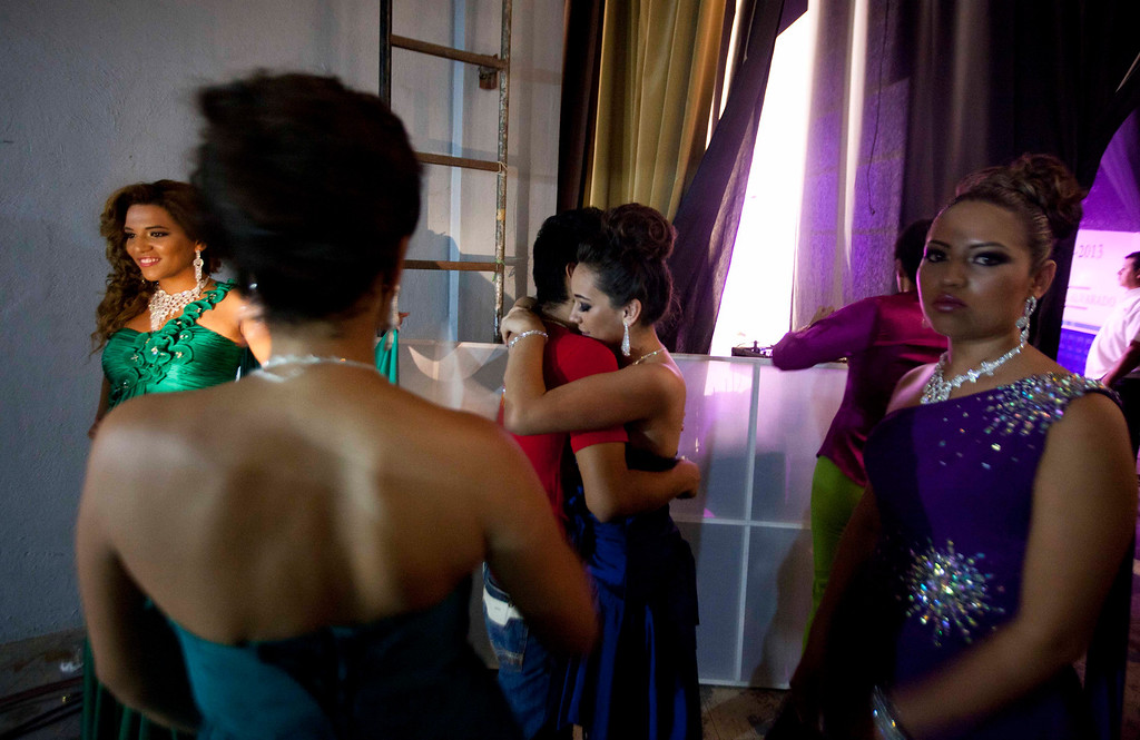 ". In this Jan. 26, 2013 photo, beauty contestant Ilce Sahagun, center right, embraces an unidentified person backstage alongside other contestants at the ""Guamuchil Carnival Queen 2013\"" beauty pageant in Guamuchil, Sinaloa state, Mexico, Mexico. The town has produced at least a Miss Mexico and more recently prides itself in saying the runner up to Miss World 2009 is a native.(AP Photo/Eduardo Verdugo)"