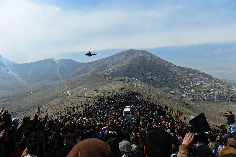 . A helicopter flies over Afghan residents as they attend the burial of Afghan Vice-President Marshal Mohammad Qasim Fahim, formerly one of the country\'s most feared warlords, at a ceremony on a hilltop in Kabul on March 11, 2014. Afghan Vice-President Marshal Mohammad Qasim Fahim died of natural causes after a turbulent life that reflected the country\'s recent past. Fahim, a leader of the Tajik ethnic minority, was senior vice-president under President Hamid Karzai, who will step down at elections next month as US-led combat forces pull out of Afghanistan after 13 years of fighting the Taliban. (WAKIL KOHSAR/AFP/Getty Images)