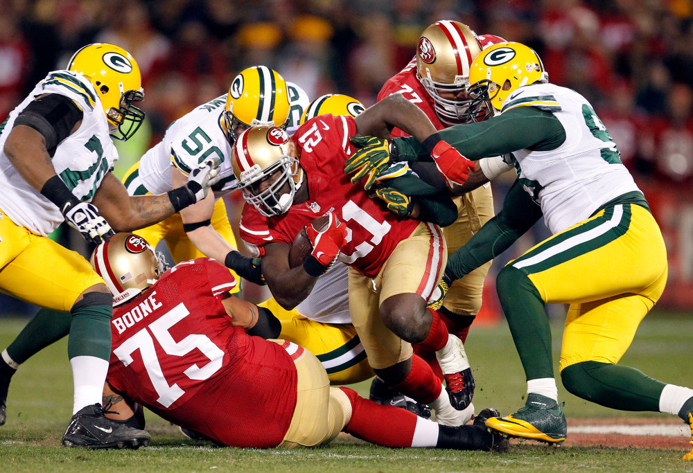 . San Francisco 49ers running back Frank Gore (21) tackled by Green Bay Packers defensive end Mike Daniels (76), inside linebacker A.J. Hawk (50), and defensive end C.J. Wilson (98) during the first half of an NFC divisional playoff NFL football game in San Francisco, Saturday, Jan. 12, 2013. (AP Photo/Tony Avelar)