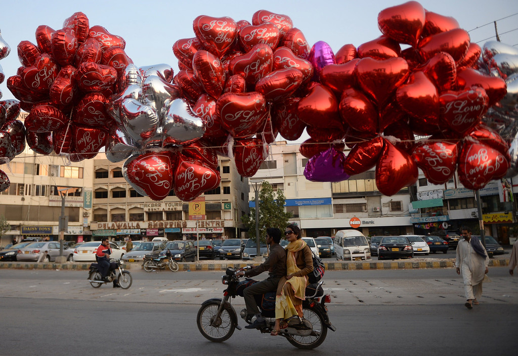 . Pakistani commuters ride past balloons hanging above a Valentine\'s stall in Karachi on February 14, 2014. At least three students were wounded in a clash at a university in the northwestern Pakistani city of Peshawar, following a dispute over Valentine\'s Day celebrations in the deeply Muslim country, police said. AFP PHOTO/Asif HASSAN/AFP/Getty Images