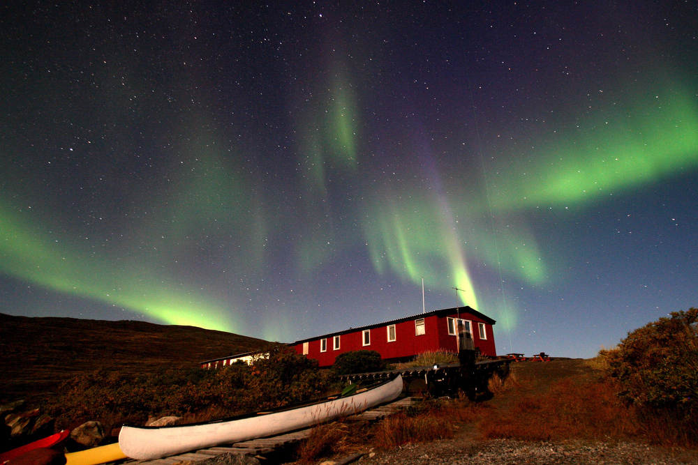 Description of . The Aurora Borealis glows over a hut near the town of Kangerlussuaq September 02, 2007, in the Greenland town of Kangerlussuaq. The Northern Lights most often occurs from September to October and from March to April and are a popular tourist attraction.  (Photo by Uriel Sinai/Getty Images)