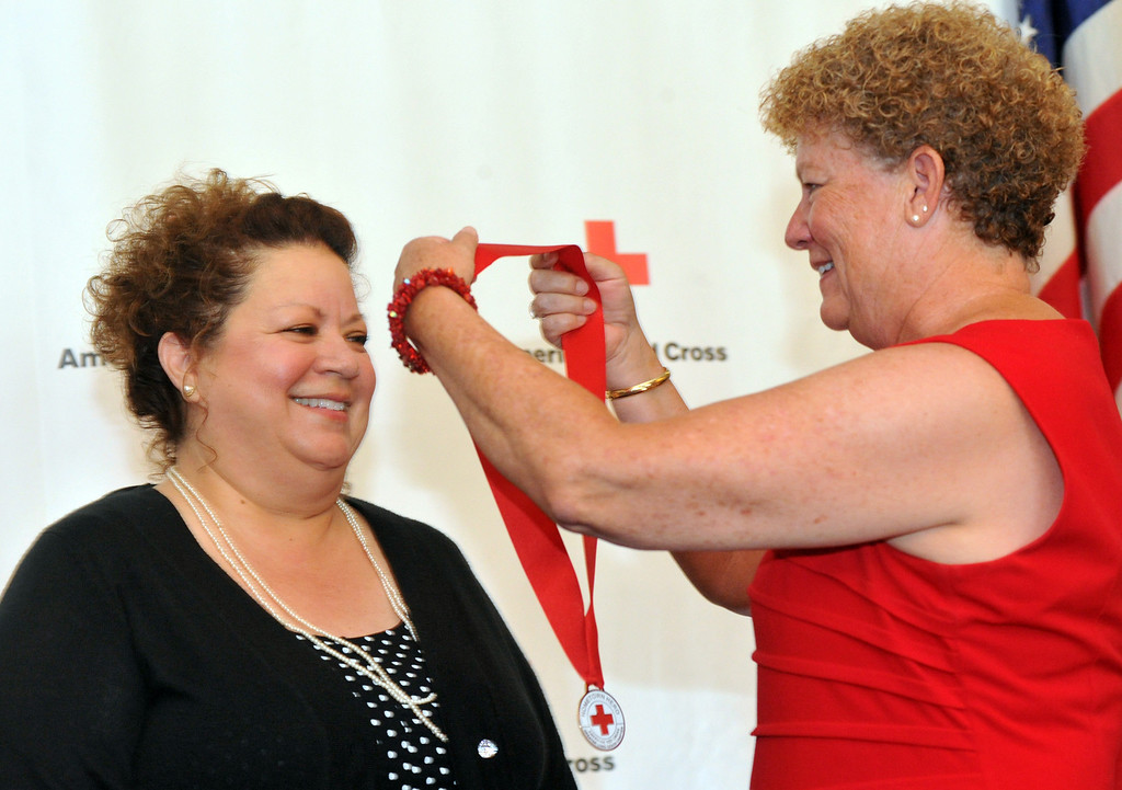 . Julia Pacheco, of Pico Rivera, receives a medal from Mollie Beck as the Rio Hondo Chapter of the American Red Cross honors 14 people for their part in performing extraordinary acts during their Hometown Heroes luncheon at the Quiet Cannon in Montebello on Thursday June 27, 2013. (SGVN/Staff Photo by Keith Durflinger)