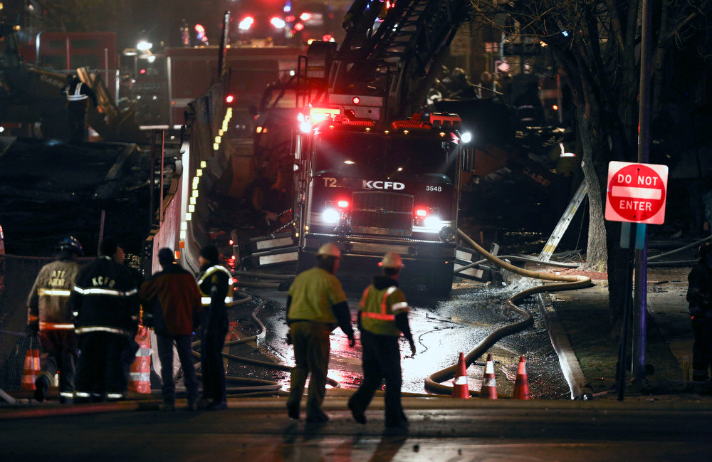 . Firemen and utility workers respond to a gas explosion and massive fire Tuesday night, Feb. 19, 2013 in the Plaza shopping district in Kansas City, Mo. A car crashed into a gas main in the upscale shopping district, sparking a massive blaze that engulfed an entire block and caused multiple injuries, police said  (AP Photo/Ed Zurga)