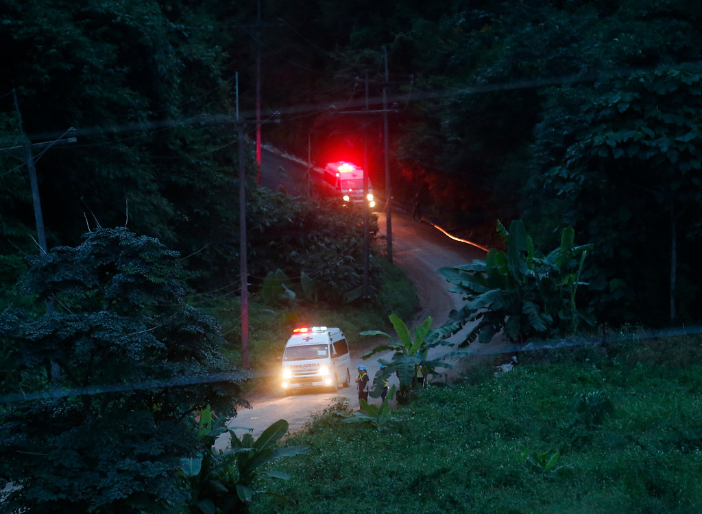 . Two ambulances with flashing lights leaves the cave rescue area in Mae Sai, Chiang Rai province, northern Thailand, Monday, July 9, 2018. The ambulance has left the cave complex area hours after the start of the second phase of an operation to rescue a youth soccer team trapped inside the cave for more than two weeks. (AP Photo/Sakchai Lalit)