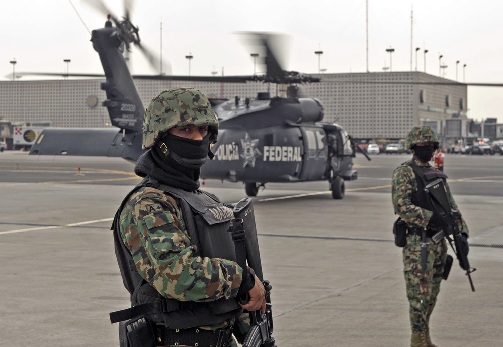 Description of . Members of the Mexican Navy stand guard next to a helicopter transporting Mexican drug trafficker Joaquin Guzman Loera aka