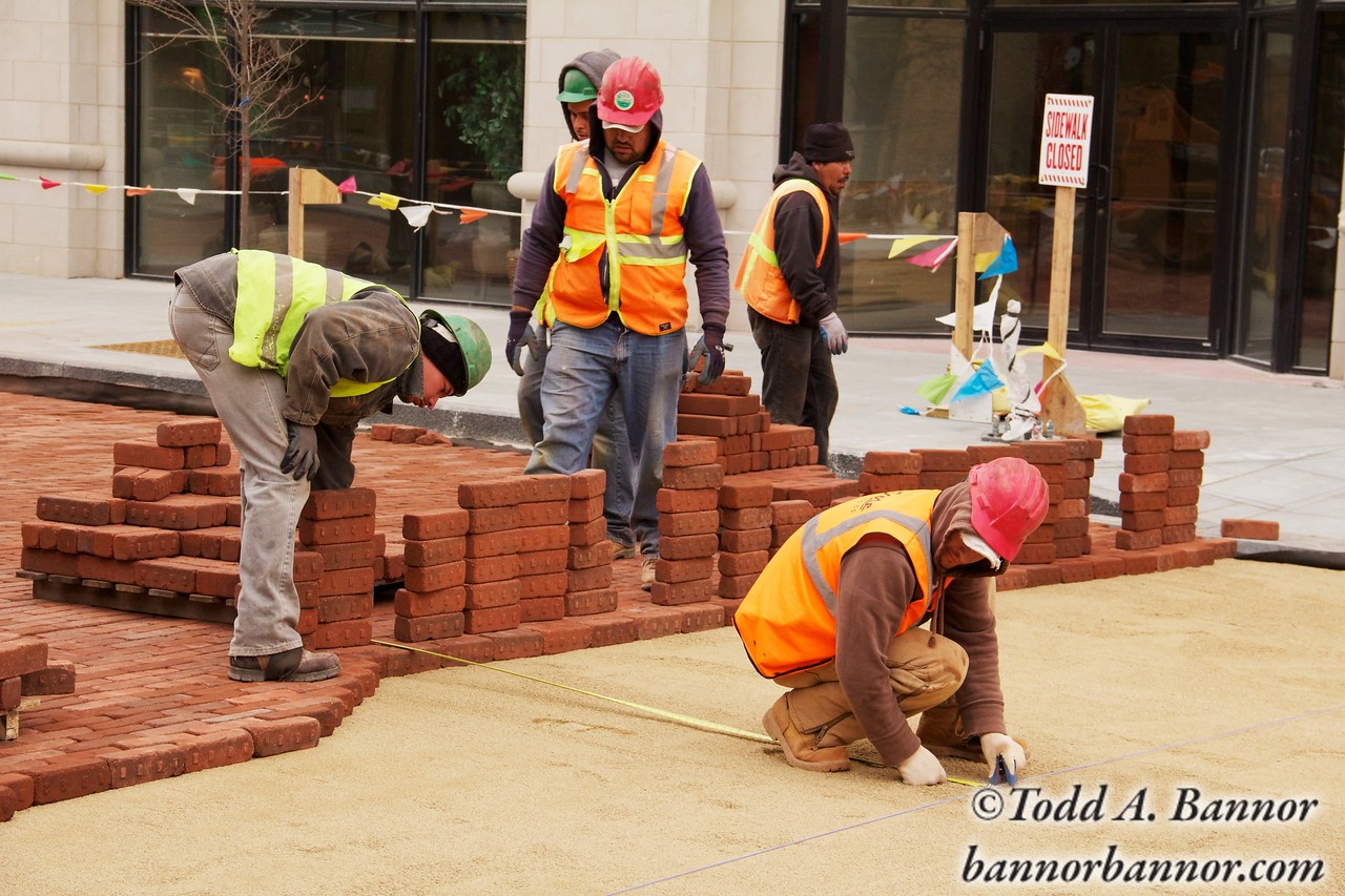 Construction workers take a measurement before laying paving bricks during Marion Street reconstruction project on Saturday November 19, 2011 in Oak Park, Illinois, USA.  Brick is being used to return the street to its early 20th century appearance and reduce storm runoff.