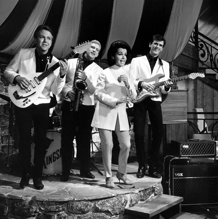 """. Actress Annette Funicello is performing with the Kingsmen, during the filming of the motion picture \""""How to Stuff a Wild Bikini,\"""" in Hollywood, Calif., on August 24, 1964.  The Kingsmen are, from left to right,: Norm Sundholm, Lynn Easton, and Mike Mitchell.  (AP Photo)"""