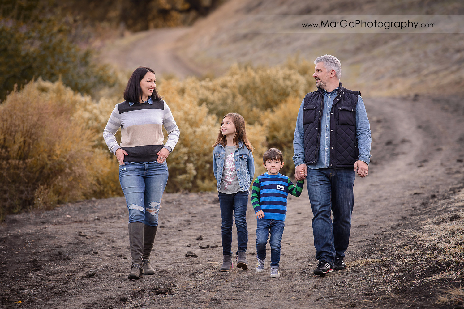 family of four wearing blue and grey clothes looking at each other and walking down the hill during photo session at Diablo Foothills Regional Park in Walnut Creek