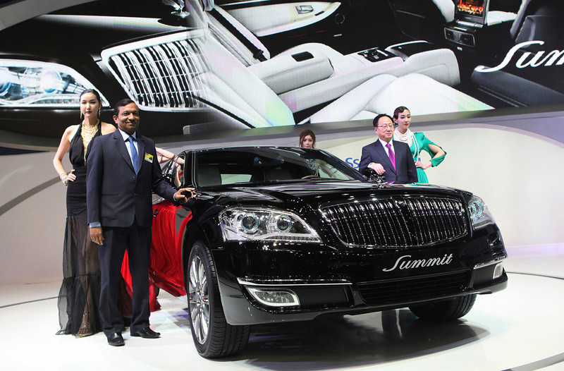 """. Pawan Kumar Goenka, president of Mahindra & Mahindra LMT., second from left, and Lee Yoo-Il, SsangYong Motor chief executive, second from right, pose with a Ssangyong\'s new model, \""""Chairman W Summit\"""" during a press day of the Seoul Motor Show in Goyang, South Korea, Thursday, March 28, 2013. The exhibition, with 384 companies from 14 countries to participate in, will be held from March 29 through April 7. (AP Photo/Ahn Young-joon)"""