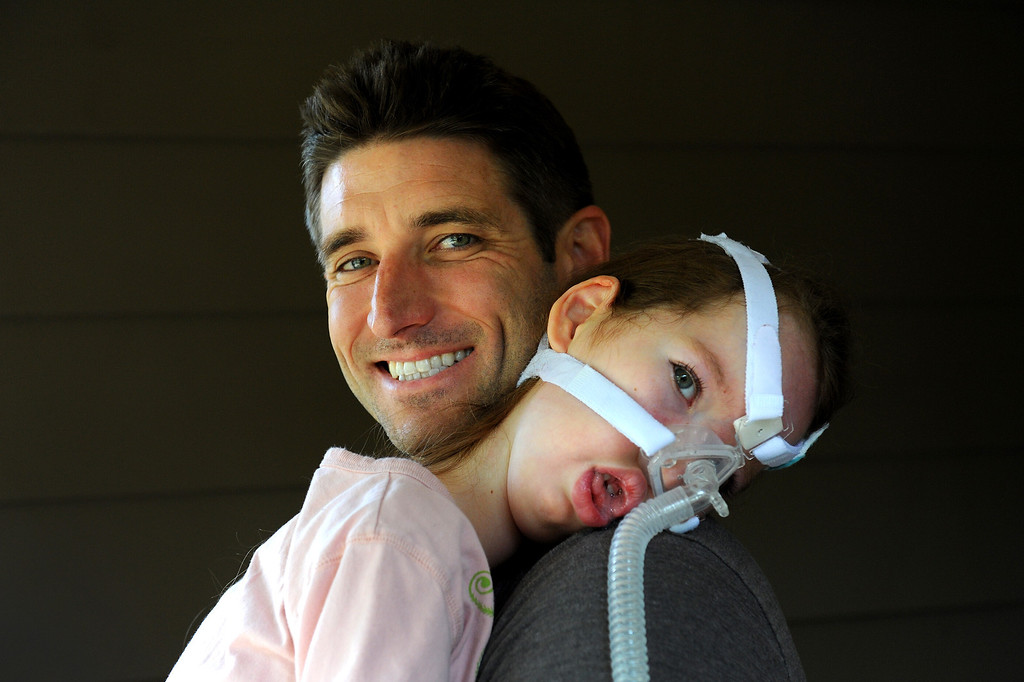 . Bill Strong holds his daughter Gwendolyn in their Santa Barbara home. Gwendolyn was born with spinal muscular atrophy and wears a tube that blows air into her lungs. (Photo by Michael Owen Baker/Los Angeles Daily News)