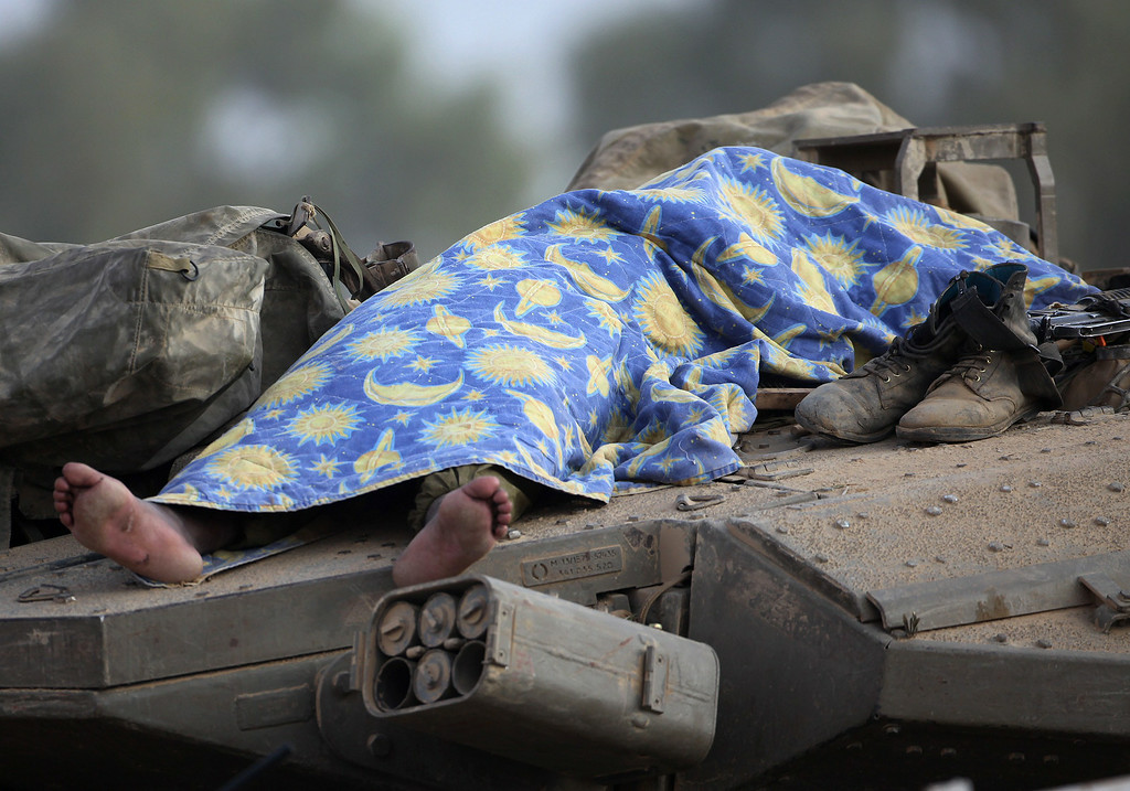 . An Israeli soldier sleeps on a tank positioned along the border between Israel and the Hamas-controlled Gaza Strip on July 29, 2014. Bloodshed in war-torn Gaza surged on with dozens more Palestinians killed as the conflict raged into a fourth week and Iran accused Israel of genocide in the tiny enclave. AFP PHOTO/ DAVID  BUIMOVITCH/AFP/Getty Images