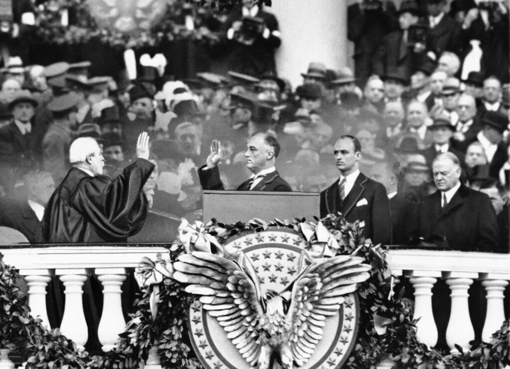 . President Franklin D. Roosevelt takes the oath of office from Chief Justice Charles E. Hughes at the inauguration, March 4, 1933. At right is Herbert Hoover and behind the president is his eldest son James Roosevelt. (AP Photo)