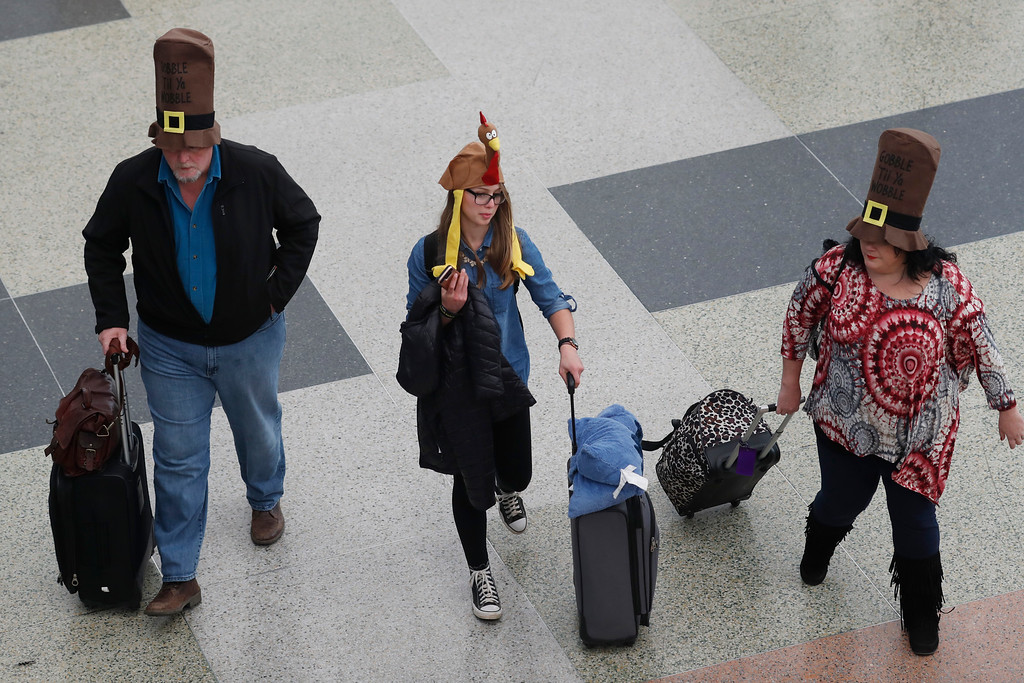 . From left, Jack, Nikki  and Rae Forbes of Asheville, N.C., wear hats to fit the holiday as they head through the terminal after arriving at Denver International Airport early Wednesday, Nov. 23, 2016, in Denver. Travelers are criss-crossing the country Wednesday, clogging airport terminals in a rush to reach their Thanksgiving Day destinations. (AP Photo/David Zalubowski)