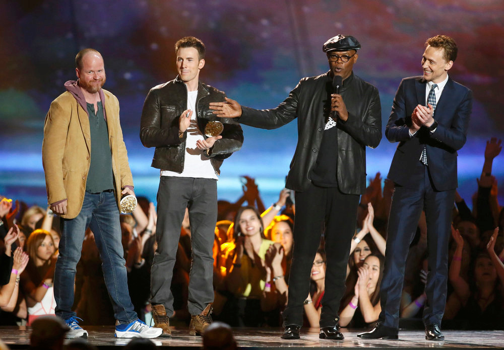 ". Samuel L. Jackson gestures towards director Joss Whedon (L) as he accepts the award for best fight from ""The Avengers\"" with fellow actors Chris Evans (2nd L) and Tom Hiddleston (R) at the 2013 MTV Movie Awards in Culver City, California April 14, 2013.  REUTERS/Danny Moloshok"