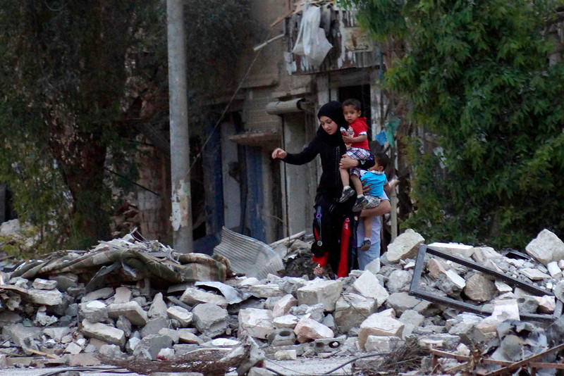 . A woman carries her child as she walks on rubble in a neighborhood in Deir al-Zor April 15, 2013.  REUTERS/Khalil Ashawi