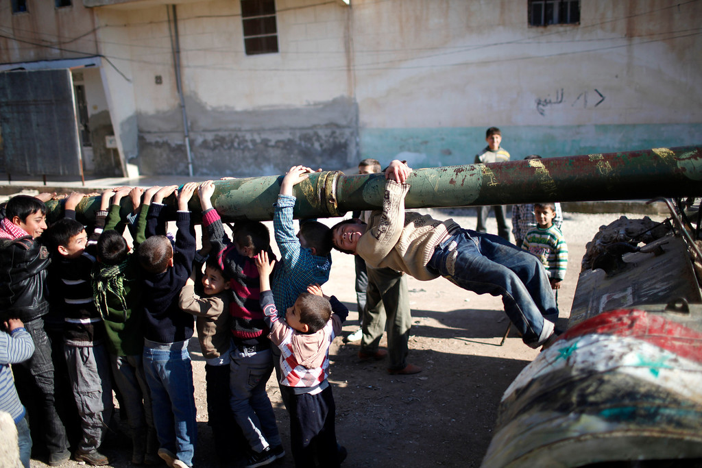 . Children hang from the barrel of a tank, which was captured by the Free Syrian Army, as it is repaired in Azaz city, north Aleppo, December 30,2012.    REUTERS/Ahmed Jadallah