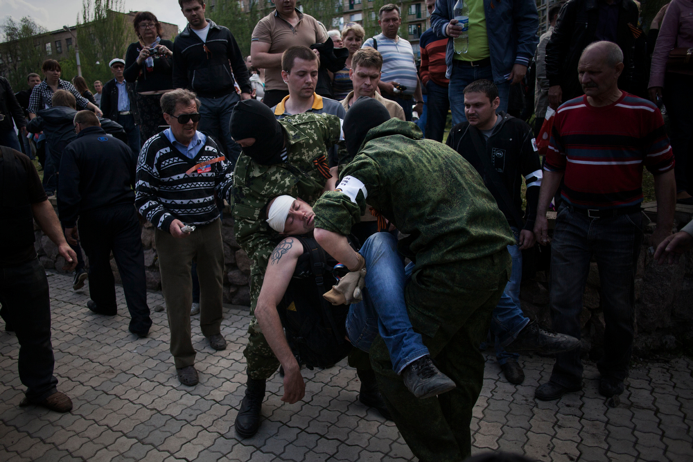 . Masked pro Russia men hold a wounded comrade during the assault of the prosecutor building, after a pro Russia demonstration during International Worker\'s Day in Donestsk, Ukraine, Thursday, May 1, 2014. Anti-government demonstrators in Donetsk have stormed the local prosecutor\'s office. The clash came after a march by several hundred people carrying flags of the Donetsk People\'s Republic, a movement that seeks either greater autonomy from the central government, or independence and possible annexation by Russia.(AP Photo/Manu Brabo)