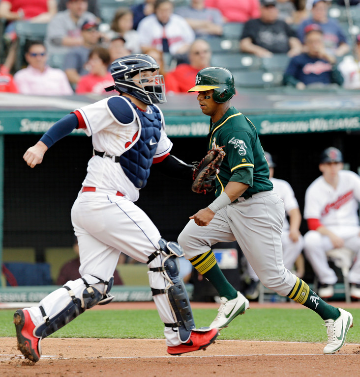 . Oakland Athletics\' Khris Davis, scores as Cleveland Indians catcher Roberto Perez defends in the fourth inning of a baseball game, Tuesday, May 30, 2017, in Cleveland. Davis scored on a double by Ryon Healy. (AP Photo/Tony Dejak)