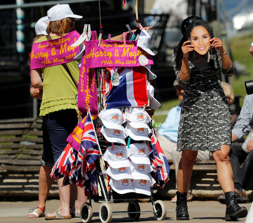 . A woman uses a Meghan Markle mask, near a street vendor in Windsor, England, Tuesday, May 15, 2018.  Preparations continue in Windsor ahead of the royal wedding of Britain\'s Prince Harry and Meghan Markle Saturday May 19. (AP Photo/Frank Augstein)