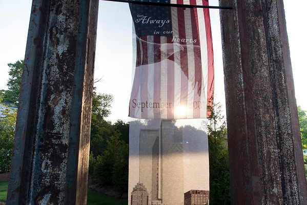 09/11/19 Wesley Bunnell | StaffrrThe Kensington Fire Department held a 9/11 memorial service on Wednesday evening in front of the department at 880 Farmington Ave. An american flag and silk screen of the twin towers is backlit as it stands between two beams salvaged from towers 1 and 2.