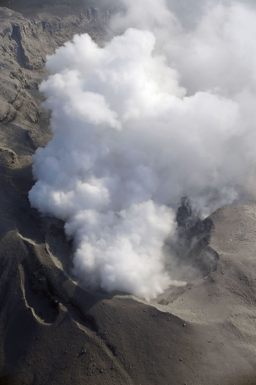 . A column of white smoke rises from the crater of Mount Shindake on Kuchinoerabu island, southern Japan Friday, May 29, 2015. The volcano erupted in spectacular fashion on the small island on Friday, spewing out rocks and sending black clouds of ash 9 kilometers (5.6 miles) into the sky. Authorities told people on the island to evacuate. (Kyodo News via AP)