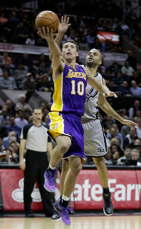 . Los Angeles Lakers\' Steve Nash (10) drives to the basket as San Antonio Spurs\' Tony Parker, right, of France, defends him during the second half of Game 2 of a first-round NBA basketball playoff series, Wednesday, April 24, 2013, in San Antonio, Texas. San Antonio won 102-91. (AP Photo/Eric Gay)
