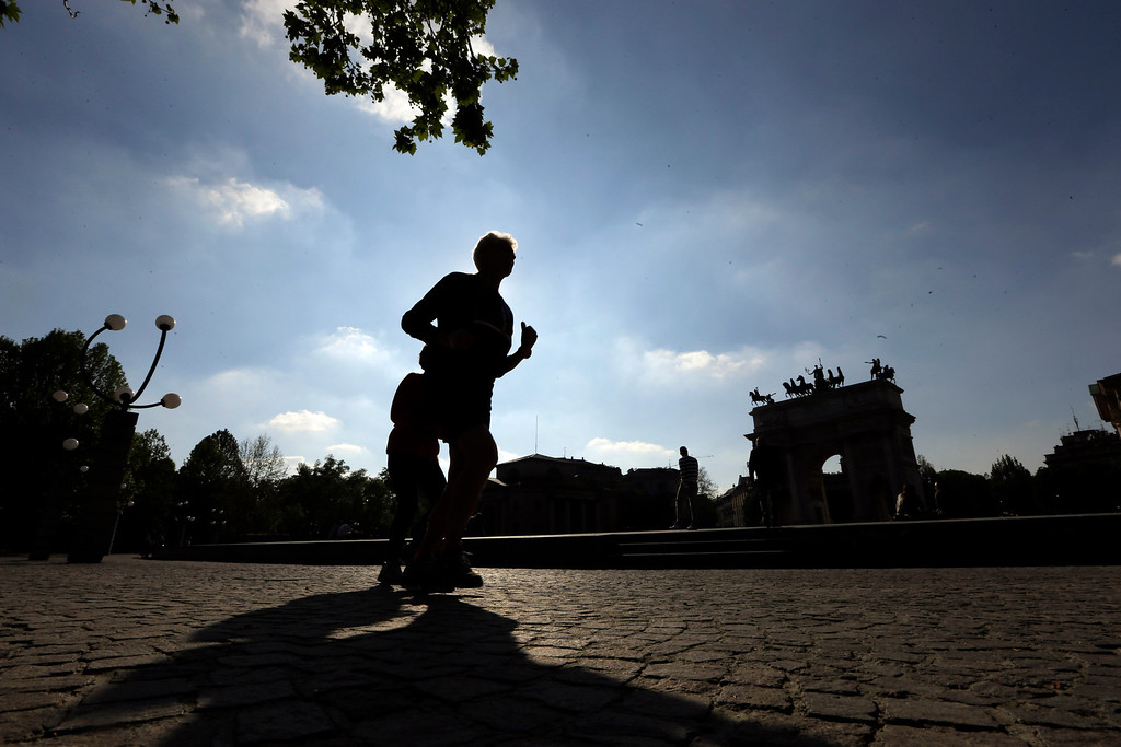 """. Runners run past the \""""Arch of Peace\"""", visible in background, in Milan, Italy, Tuesday, April 22, 2014. People across the globe hold events to celebrate the Earth\'s environment and spread awareness on how to conserve its natural resources on Earth Day, observed annually on April 22. (AP Photo/Luca Bruno)"""
