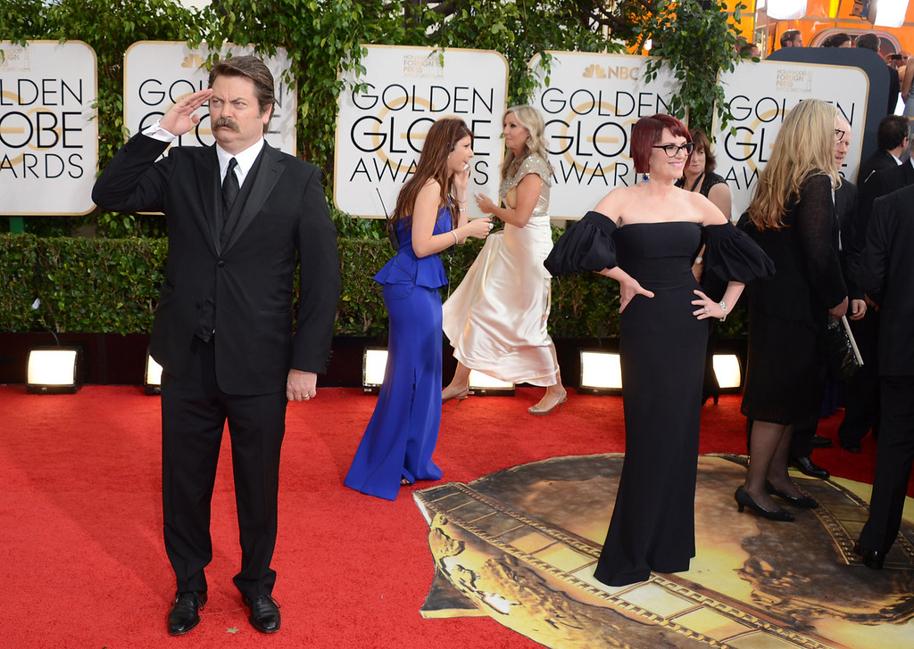 . Nick Offerman, left, salutes the crowd as his wife Megan Mullally poses at the 71st annual Golden Globe Awards at the Beverly Hilton Hotel on Sunday, Jan. 12, 2014, in Beverly Hills, Calif. (Photo by Jordan Strauss/Invision/AP)