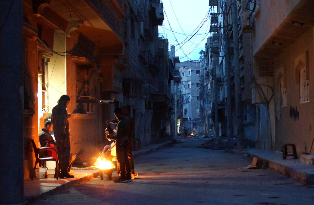 . Members of the Free Syrian Army stand around a fire while they guard a neighborhood in Deir al-Zor on April 19, 2013. Picture taken April 19, 2013. REUTERS/ Khalil Ashawi