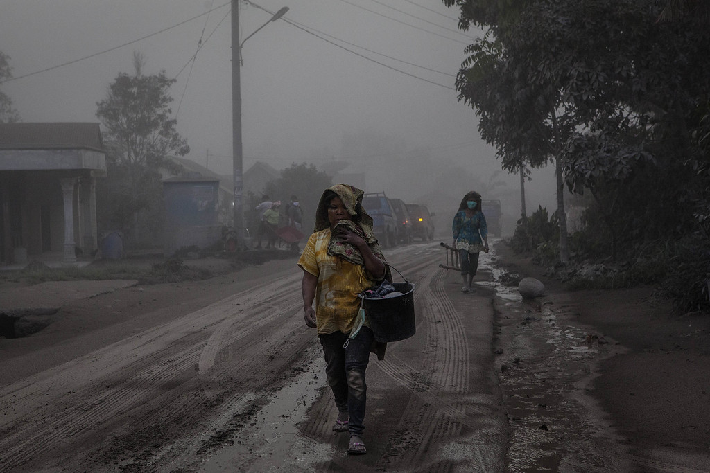 . A woman walks on a road covered with ash following a further eruption of the Mount Sinabung on October 13, 2014 in Berastagi, Karo district, North Sumatra, Indonesia.  (Photo by Ulet Ifansasti/Getty Images)