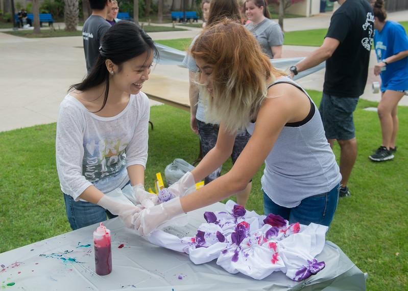 Nga Tran (left) helps fellow student Ingrid Fernandez tie-dye her lab coat.