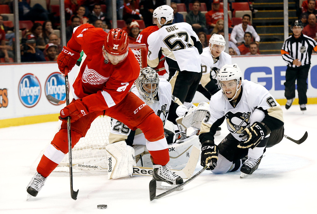 . Pittsburgh Penguins defenseman Scott Harrington (6) defends Detroit Red Wings\' Tomas Tatar (21), of Slovakia, in the second period of a NHL preseason hockey game in Detroit Wednesday, Oct. 1, 2014. (AP Photo/Paul Sancya)