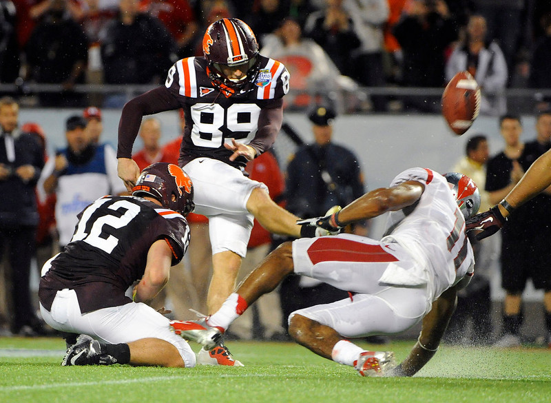 . Virginia Tech kicker Cody Journell (89) gets the hold from quarterback Trey Gresh (12) while booting the go-ahead field goal in overtime in front of Rutgers defensive back Logan Ryan (11) during an NCAA college football Russell Athletic Bowl game on Friday, Dec. 28, 2012, in Orlando, Fla. (AP Photo/Brian Blanco)