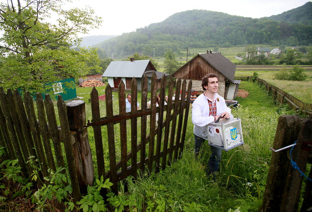 . Member of the election commission in a traditional Ukrainian costume carries a mobile ballot box during voting in a presidential election at polling station in the village of Fiyna in the Lviv region of western Ukraine, Sunday, May 25, 2014. (AP Photo/Petro Zadorozhnyy)