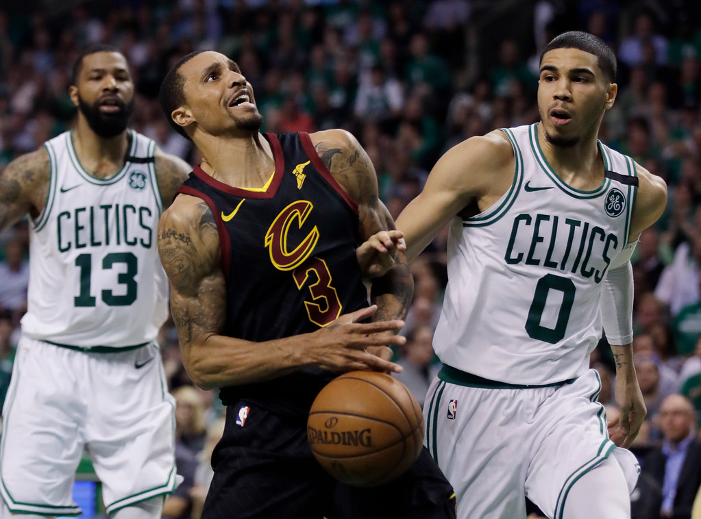 . Cleveland Cavaliers guard George Hill (3) loses control of the ball against Boston Celtics forward Jayson Tatum (0) as Celtics forward Marcus Morris (13) watches, left, during the second quarter of Game 5 of the NBA basketball Eastern Conference Finals, Wednesday, May 23, 2018, in Boston. (AP Photo/Charles Krupa)