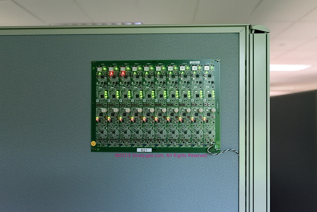 Lighting control board being tested on the side of a Crestron engineering cubicle