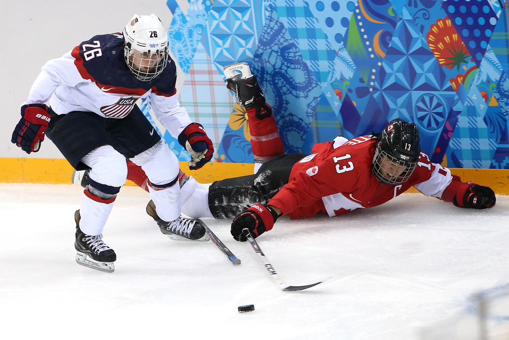 . Kendall Coyne #26 of the United States and Caroline Oullette #13 of Canada go for a loose puck in the second period during the Women\'s Ice Hockey Preliminary Round Group A game on day five of the Sochi 2014 Winter Olympics at Shayba Arena on February 12, 2014 in Sochi, Russia.  (Photo by Bruce Bennett/Getty Images)