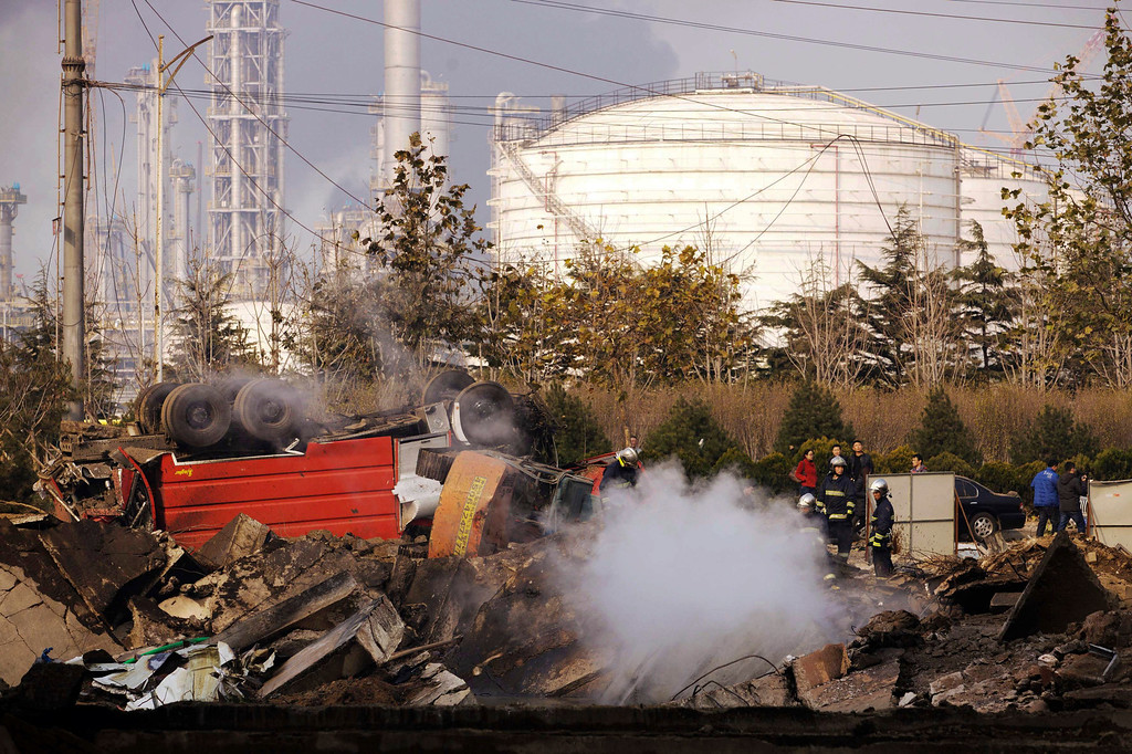 . Firefighters work on a damaged site following a pipeline explosion in Qingdao in east China\'s Shandong province Friday, Nov. 22, 2013. (AP Photo)