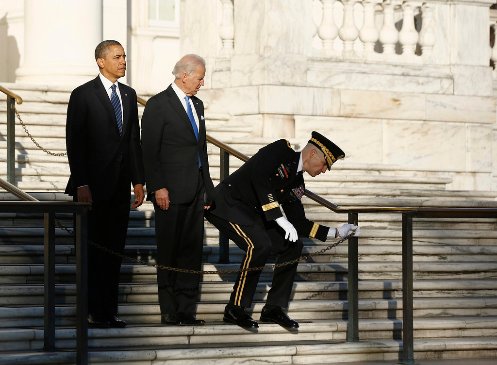 . U.S. President Barack Obama and Vice President Joe Biden wait as U.S. Army Military District of Washington Major General Michael Linnington struggles to unchain a fence before they lay a wreath at the Tomb of the Unknown Soldier at Arlington National Cemetery near Washington, January 20, 2013. Obama will take the official oath of office in a small, private ceremony at the White House on Sunday, setting a more subdued tone for his second inauguration than his historic swearing-in four years ago. Following a wreath-laying ceremony at Arlington National Cemetery, Obama will be sworn in at the White House at 11:55 a.m. EST (1655 GMT).      REUTERS/Jason Reed